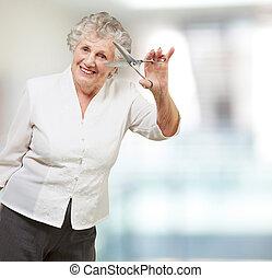 Senior woman holding scissors, indoor