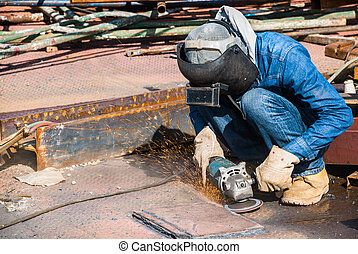 professional worker in construction industry grinding metal...