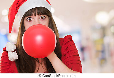 woman blowing balloon and wearing a christmas hat at the...