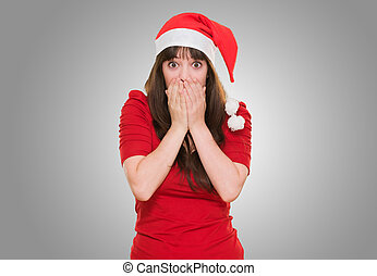 surprised christmas woman covering her mouth against a grey...