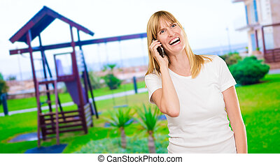 Woman Talking On Cell Phone at a park, outdoor
