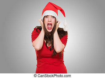 furious woman wearing a christmas hat against a grey...