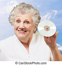 Senior woman holding cd, outdoor
