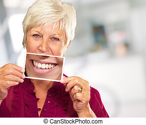 Senior Woman With Manifying Glass Showing Teeth, Background