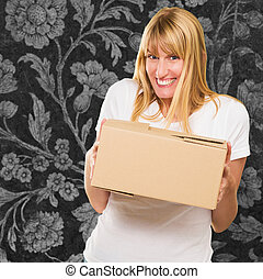 Woman Holding Cardboard box against a floral pattern...