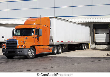 Semi truck by the warehouse - Orange semi truck by the door...