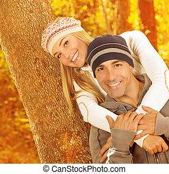 Happy couple hugging in autumn park
