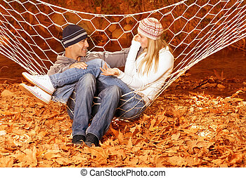 Couple talking in hammock - Happy couple speaking and...