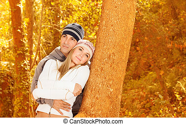 Happy lovers in autumn park