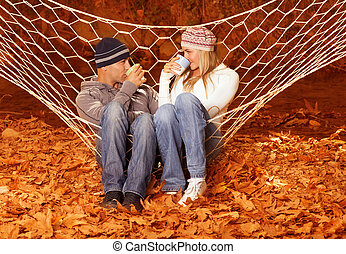 Young couple drink tea in hammock