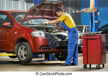 auto mechanic at work with wrench - One young auto mechanic...