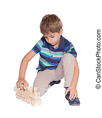 Boy playing with a toy train. Isolated over white background.