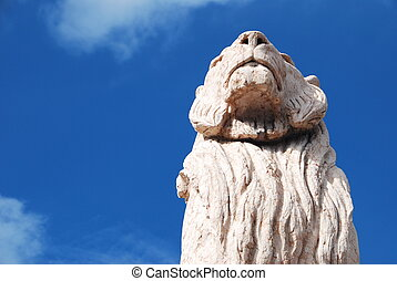 Stone lion in perspective over a blue sky