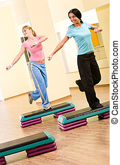 Exercising - Two sporty women practicing physical exercises...