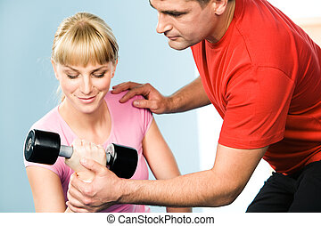 Assisting - Image of pretty girl exercising with barbell in...