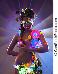Beauty woman with glowing make-up posing in dark