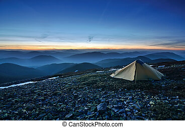 Tourist tent in the rocky mountains and first star on the...