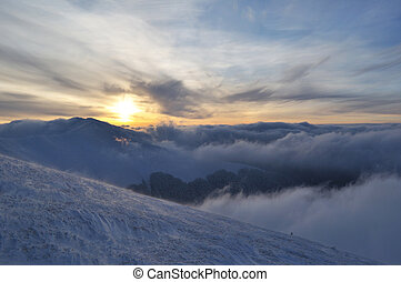 Setting sun in cloudy winter mountains