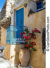 Street scene on Santorini - Blue door with flowers in...