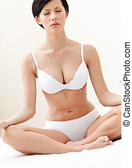 Woman meditates sitting on the wide bed, white background