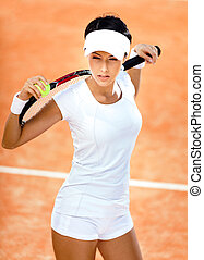 Athletic woman keeps tennis racket and ball on her shoulders...