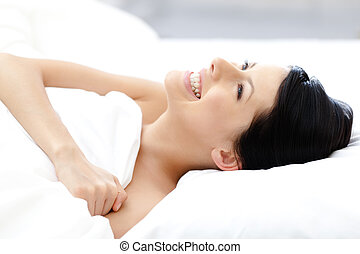 Laughing sexy girl tries to fall asleep in bed with white...