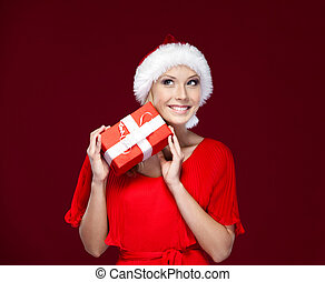 Beautiful lady in Christmas cap hands a present