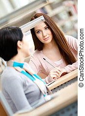 Two young women communicate sitting at the desk