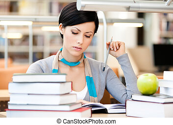 Pretty woman reads sitting at the desk - Woman with green...