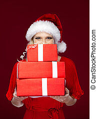 Beautiful woman in Christmas cap hands a set of presents