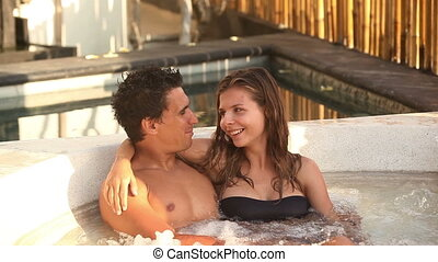 Honeymoon - Attractive couple relaxing in spa Jacuzzi during...