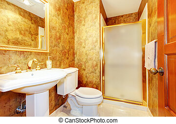 Golden antique bathroom with white toilet and sink.