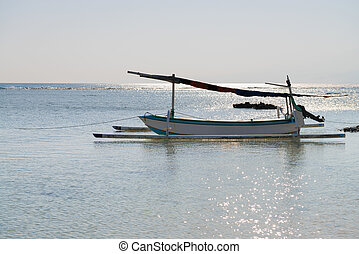 Traditional indonesian boat on the surf of blue sea and back...