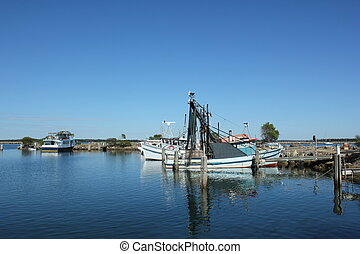 A fishing boat is dock at shore