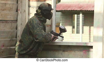 Paintball - Paintball sport player in protective uniform and...