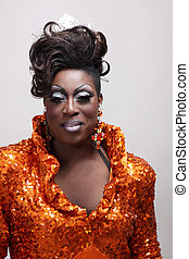Drag queen wearing an orange gown with sequins.