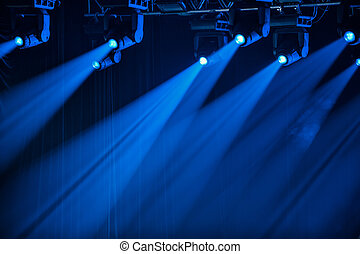 Blue stage spotlights shine in one direction