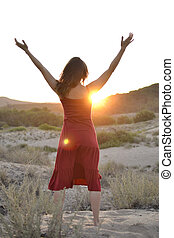 Greeting the sun - Beautiful young woman raising her arms to...
