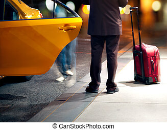 Man catching a taxi - Man in suite catching a yellow cab at...