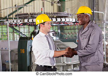 manager handshaking with african american worker - factory...