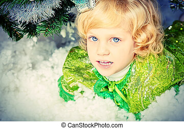 under tree - Happy little girl in Christmas dress lying in...