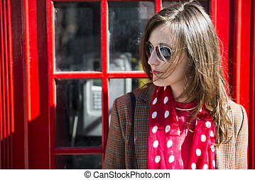 Fashionable young woman leaning on red phone booth -...