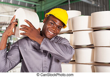 textile factory worker carrying raw material on his shoulder
