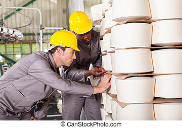 industrial workers checking raw material