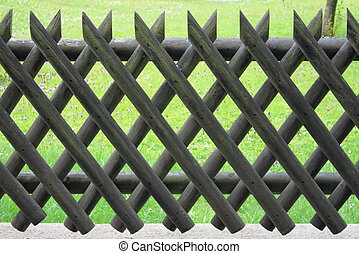Wooden fence with lattice on a green grass background