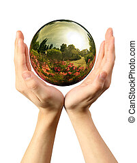 Woman hands holding a glass globe with nature reflection