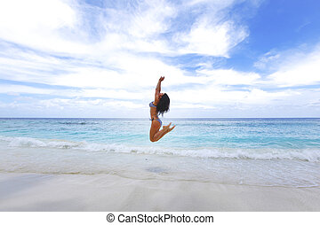 Young woman jumping on a beach - Young beautiful woman...
