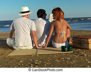 woman cheating on boyfriend by sea shore - young man...