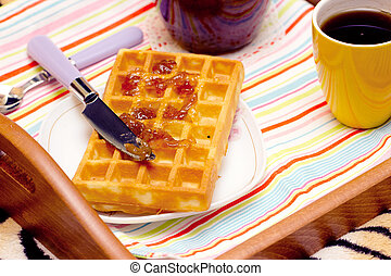 Close-up of a waffle and knife, spread the jam
