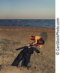 young businessman, burried in sand, seashore, woman -...
